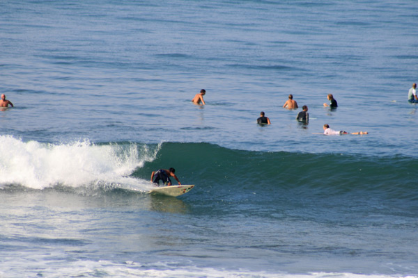 samir catching a lot of waves in a crowded lineup